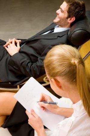 Homem sorridente deitado numa poltrona a receber psicoterapia de uma terapeuta feminina que escreve num papel