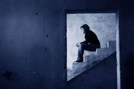 mulher sentada em degraus de uma casa inacabada, com ar pensativo, vista através da abertura de uma porta