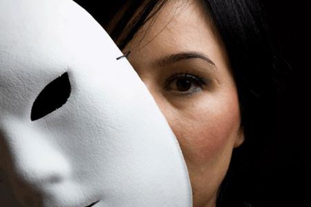 mulher esconde-se atrás de uma máscara branca