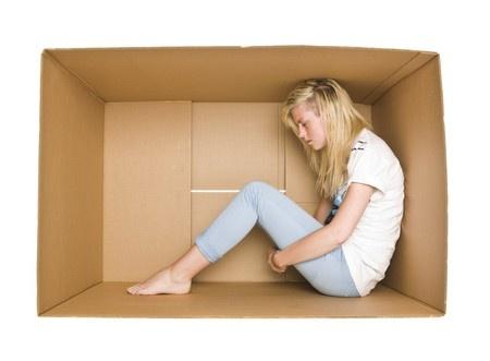Mulher com expressão de sofrimento encolhe-se dentro de caixa de cartão