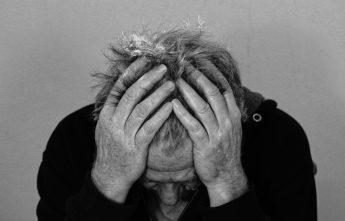 homem de idade com as mãos na cabeça denunciando sofrimento e desespero característicos de problemas de saúde mental, como depressão e ansiedade