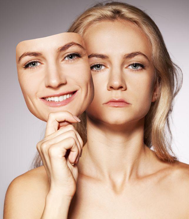 mulher infeliz segurando uma máscara com a sua cara feliz, representando as variações de humor na Depressão Bipolar