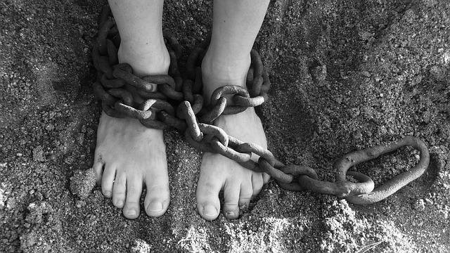 pés de mulher presos por cadeado a uma relação de violência doméstica