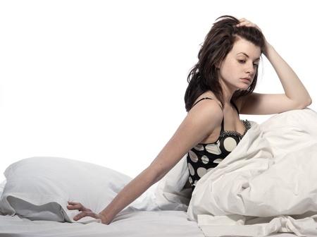 mulher sentada na cama debaixo do cobertor passa a mão no cabelo frustrada com aspeto de não conseguir dormir