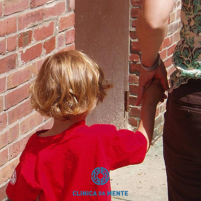 Criança de costas de mão dada com a mãe no seu primeiro dia de escola