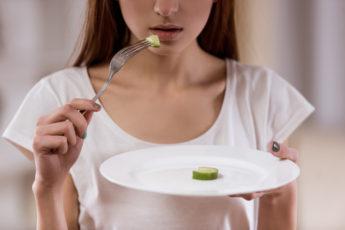 jovem a comer uma pequena porção