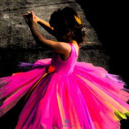 menina de vestido colorido em fundo negro