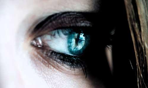 olho de mulher com expressão triste com reflexo intenso