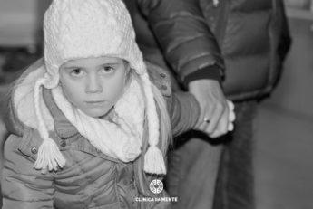 menina de gorro e mão dada a adulto enfrenta a câmara com expressão impenetrável