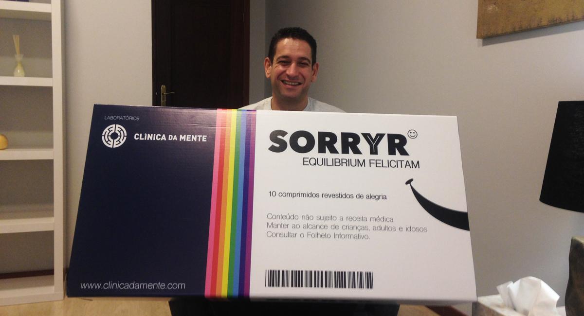 Carlos Cristovão sorri, recuperado, com uma caixa de SORRYR