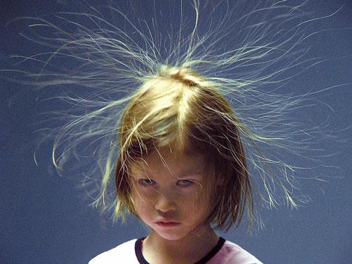 criança elétrica com cabelos no ar