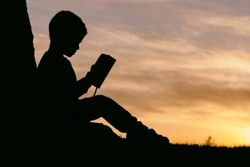 jovem isolado e tímido a ler um livro no fim de tarde