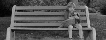 criança vítima de bullying sentada num banco de jardim
