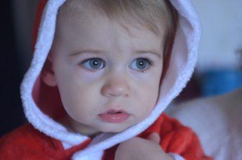 criança com olhar assustado e intimidado vestido de pai natal
