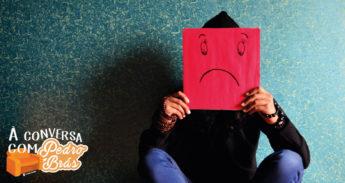 Pessoa segura num papel com uma cara triste desenhada ilustrando insatisfação