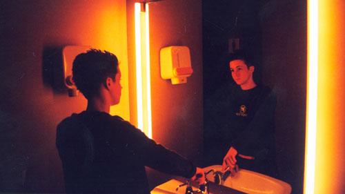 rapaz olha-se no espelho num ambiente escuro, ilustrando a importância da imagem para os jovens