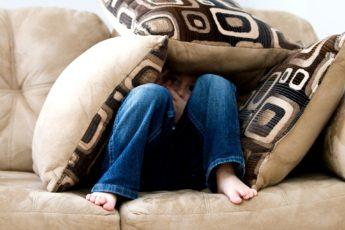 menino escondido entre almofadas com medo
