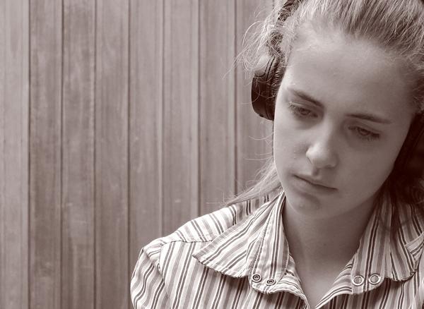 menina com expressão triste quase a chorar com auscultadores
