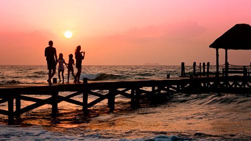 pais atentos e conscientes passeiam com os filhos num pontão da praia ao por do sol, transparecendo tranquilidade e harmonia em família