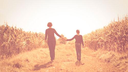 mae e filha de maos dadas no campo em tranquilidade e mindfulness