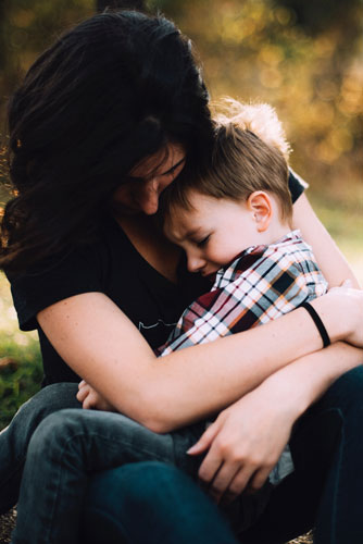 mãe consola o seu filho, cuidando da saude mental na infancia