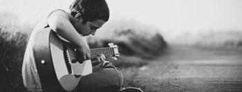 rapaz tímido toca guitarra sozinho ao ar livre