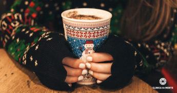 rapariga segura copo de café com camisola e copo alusivos ao natal