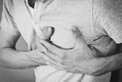 homem com dor no peito e falta de ar coloca as mãos sobre o coração acelerado em panico