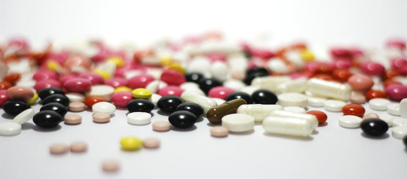 comprimidos espalhados ilustrando o excesso de medicação e a abordagem farmacológica