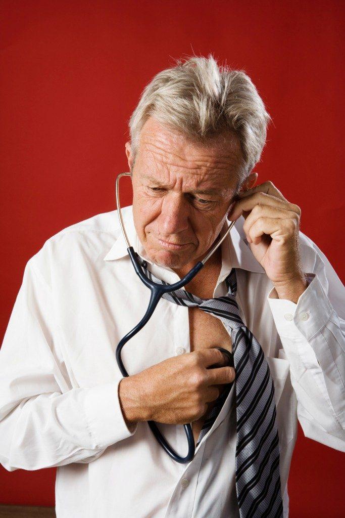 homem de idade ausculta-se a si próprio, com ar preocupado, demonstrando hipocondria