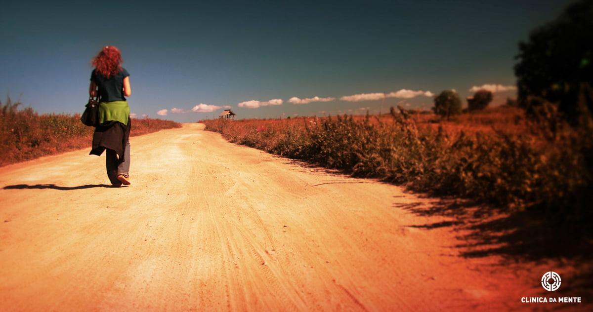 Mulher a caminhar por uma estrada de terra, simbolizando o sentimento de estar perdida e sozinha no sofrimento