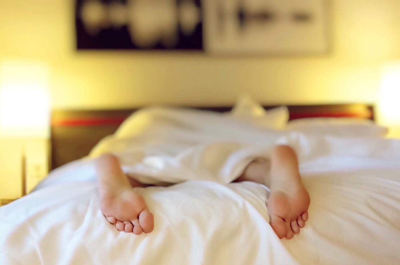 homem na cama com pés de fora