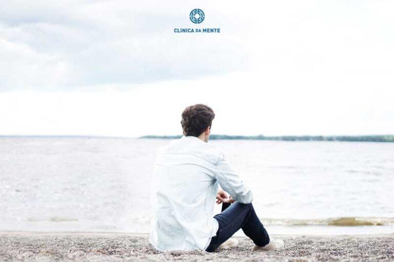 homem sentado na praia a olhar o mar pensativo