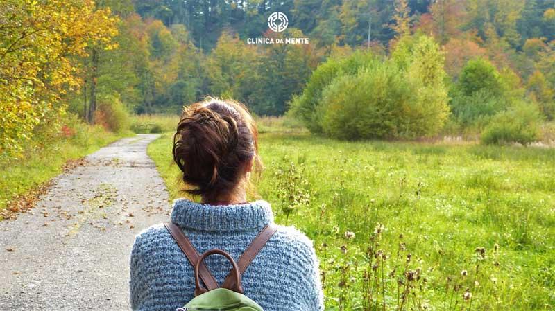 mulher prepara-se para uma nova etapa perante um caminho a percorrer no meio do campo