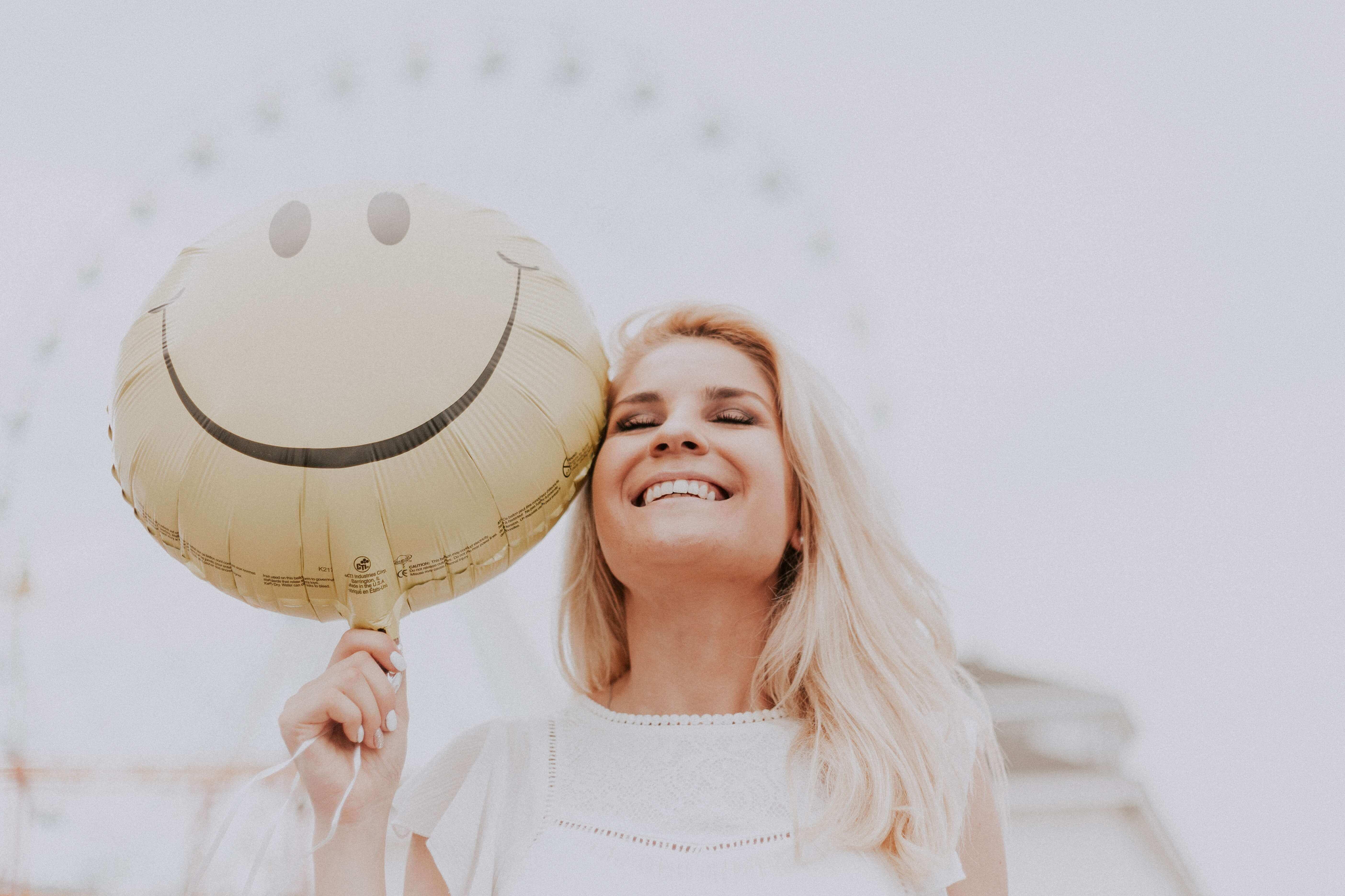 mulher com balão com um smiley