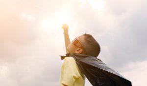 criança com óculos e saco de plástico a imitar uma capa em pose de super herói a olhar para o céu com um dos braços esticados