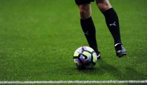pernas de um jogador de futebol junto à bola, prestes a marcar um penálti, como forma de ilustrar a ansiedade na prática desportiva